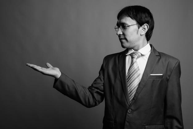 Perto de um jovem empresário asiático usando óculos