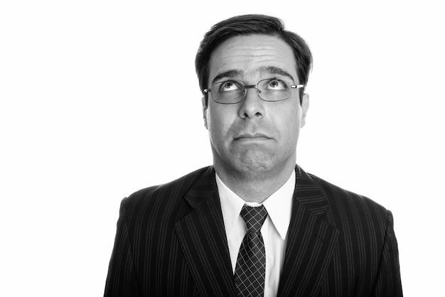 Perto de um jovem empresário persa pensando enquanto olha para cima com óculos isolados