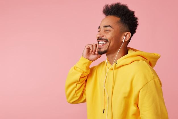 Perto de um jovem feliz afro-americano com capuz amarelo, curtindo a nova música legal de sua banda favorita em fones de ouvido, em pé com os olhos fechados e sorrindo amplamente.