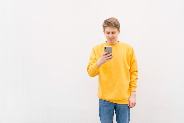 Perto de um jovem feliz digitando mensagem no smartphone