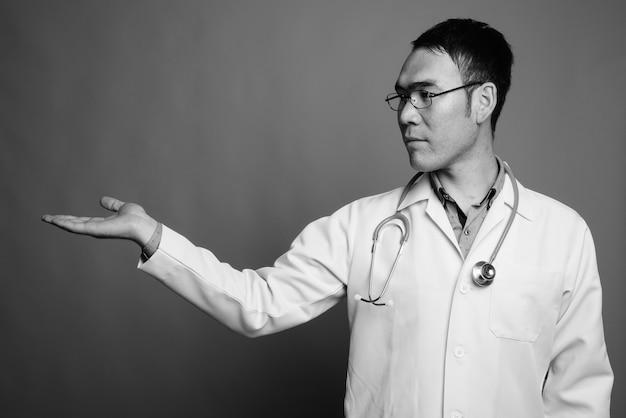 Perto de um jovem médico asiático usando óculos