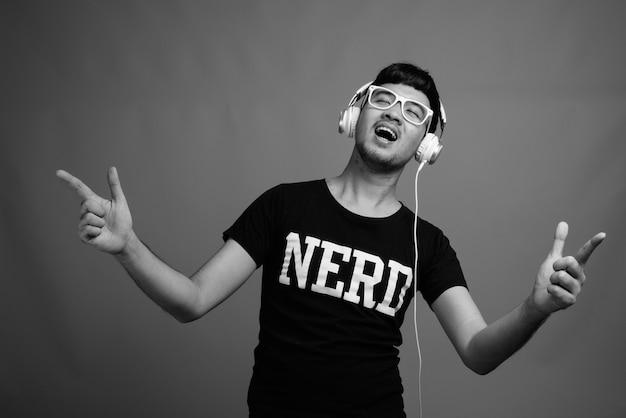 Perto de um jovem nerd asiático usando óculos enquanto ouve música