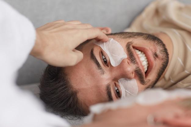 Perto de um jovem sorridente usando adesivos no rosto enquanto estava deitado no sofá com o namorado, copie o espaço