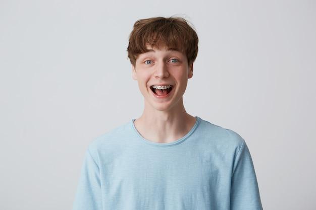 Perto de um jovem surpreso e animado com cabelo curto e desgrenhado e aparelho nos dentes