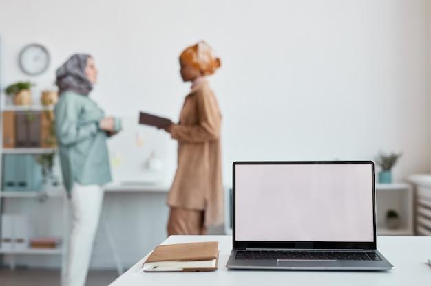 Perto de um laptop aberto com uma tela em branco e duas mulheres étnicas trabalhando em segundo plano, copie o espaço