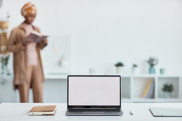 Perto de um laptop aberto com uma tela em branco e mulheres étnicas trabalhando em segundo plano, copie o espaço