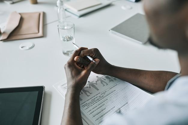Perto de um médico afro-americano sentado na mesa enquanto preenche formulários na clínica, copie o espaço