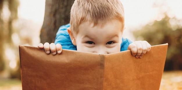 Perto de um menino bonitinho se escondendo atrás de um livro ao ar livre na natureza, olhando para a câmera.