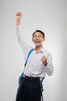 Perto de um menino sorridente, usa um uniforme escolar, carrega uma mochila e levanta a mão
