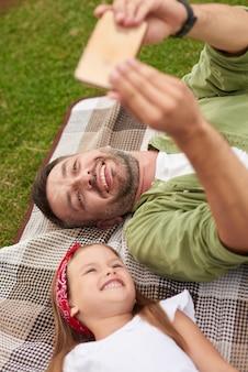 Perto de um pai alegre e sua filhinha alegre sorrindo enquanto tirava fotos de selfie