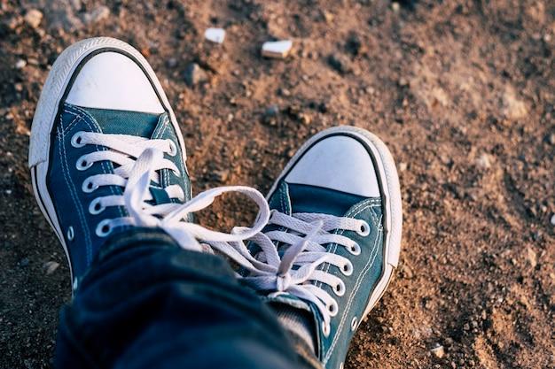 Perto de um par de tênis, sapatos azuis e jeans