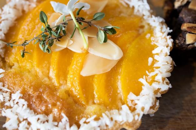 Perto de um pedaço de torta de pêssego com rodelas de amêndoa e flocos de coco.