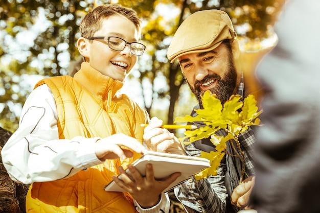 Perto de um professor e um pequeno aluno na floresta de outono tendo uma aula de ecologia em um dia bom