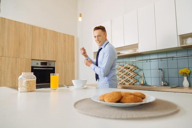 Perto de um saboroso café da manhã em cima da mesa com um homem simpático e positivo em pé ao fundo