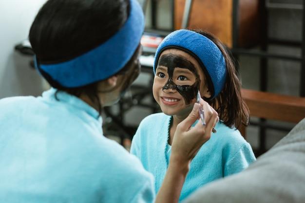 Perto de um sorriso de garota fofa enquanto usa uma máscara facial de argila preta com sua mãe em casa Foto Premium