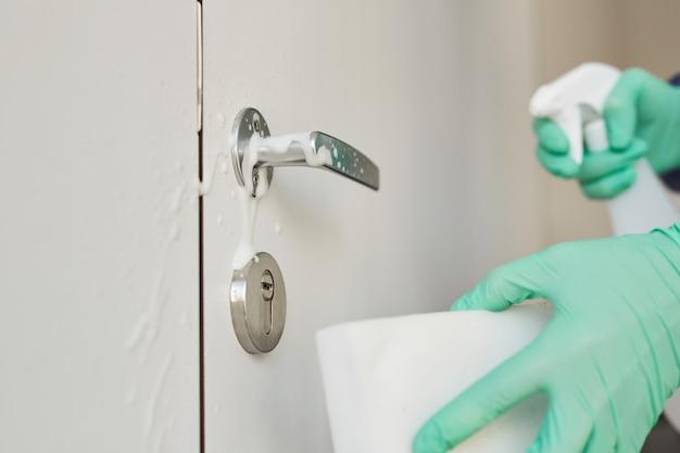 Perto de um trabalhador de limpeza irreconhecível usando luvas, limpando maçanetas com spray desinfetante,