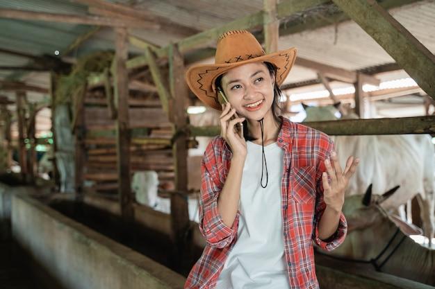 Perto de uma agricultora em pé com chapéu de cowboy, faça uma chamada usando o smartphone no fundo da fazenda