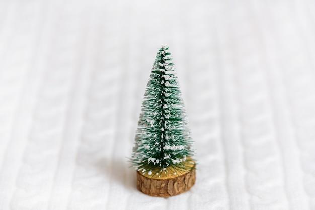 Perto de uma árvore de natal de brinquedo na cama
