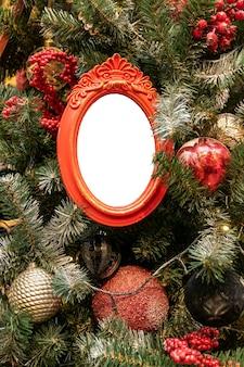 Perto de uma árvore de natal decorada com enfeites de cores prateadas vermelhas e maquete de molduras de fotos vazias