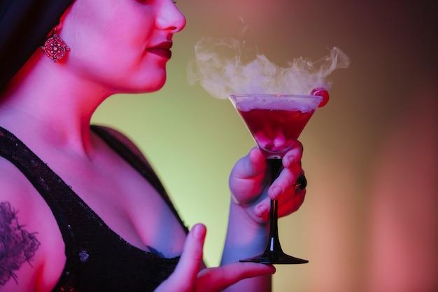 Perto de uma bebida alcoólica vermelha com fumaça de halloween