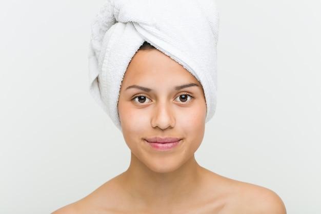 Perto de uma bela e natural jovem hispânica com uma toalha na cabeça