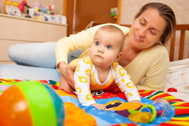 Perto de uma bela jovem mãe carinhosa ensina as cores a sua encantadora filha de seis meses