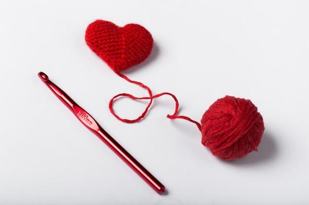 Perto de uma bola de lã e forma de coração em fundo branco. fio de lã em forma de coração. love crochet.