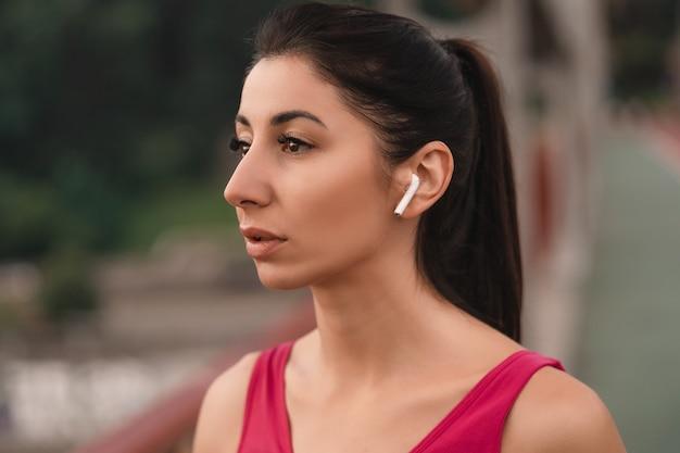 Perto de uma bonita esportista ouvindo música com fones de ouvido sem fio e sonhando, apreciando a paisagem urbana