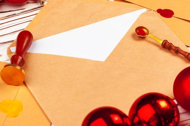 Perto de uma carta de natal com selo de cera carimbo na mesa de madeira