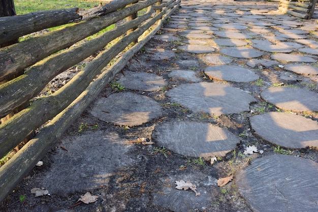 Perto de uma cerca de madeira feita de toras, há um pavimento de madeira feito de muitos tocos redondos de madeira cavados no solo de várias formas.