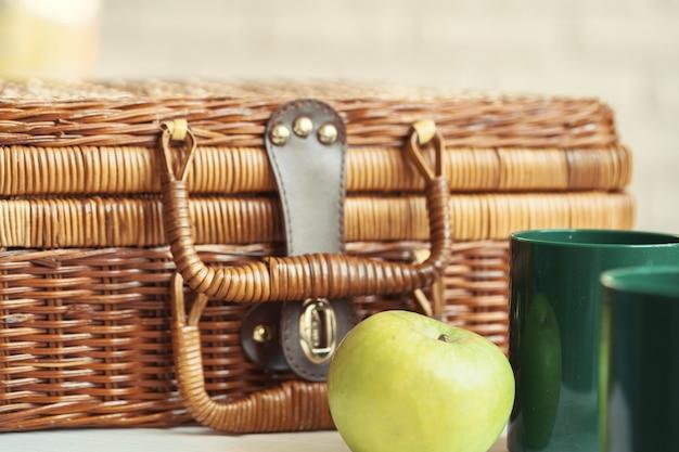 Perto de uma cesta de madeira com louça na mesa branca