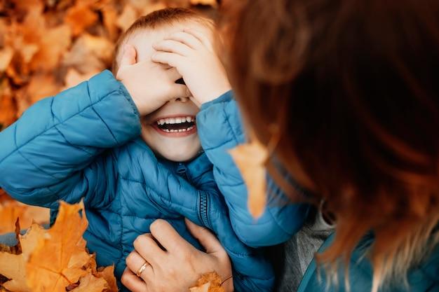 Perto de uma criança feliz rindo enquanto esconde o rosto, brincando com sua mãe, enquanto a mãe está fazendo cócegas nele ao ar livre.