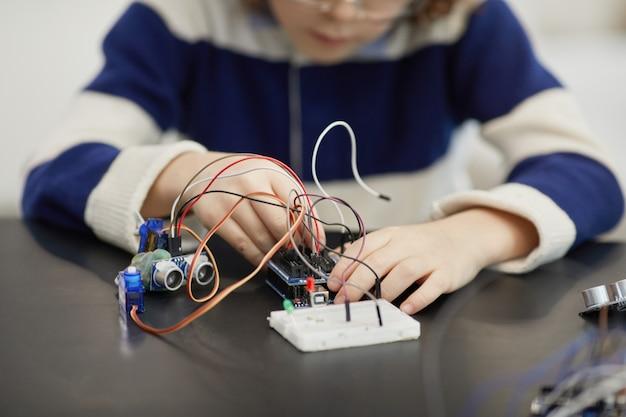 Perto de uma criança irreconhecível experimentando circuitos elétricos enquanto constrói robôs durante a aula de engenharia na escola