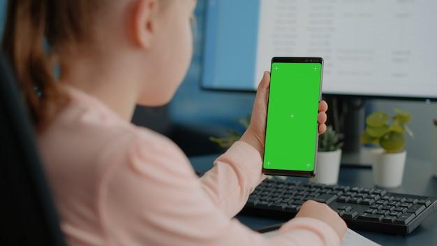 Perto de uma criança segurando uma tela verde no smartphone