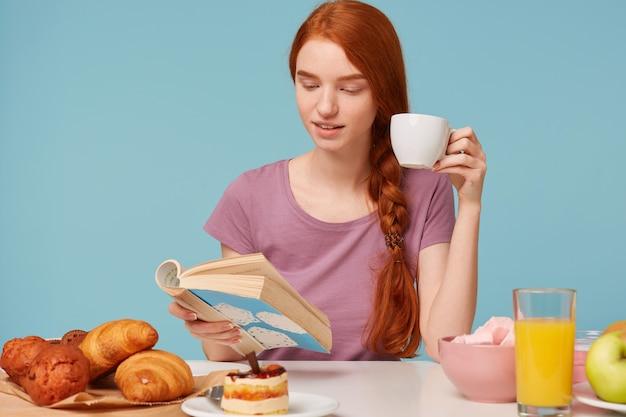 Perto de uma encantadora mulher ruiva com cabelo trançado, sentada à mesa, bebendo em um copo branco