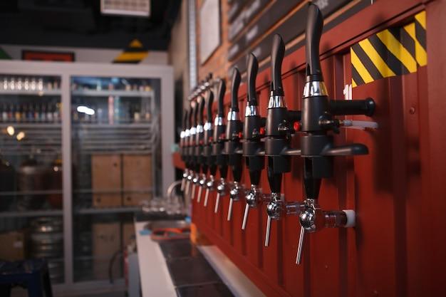 Perto de uma fila de torneiras de cerveja em um bar de cerveja local, copie o espaço