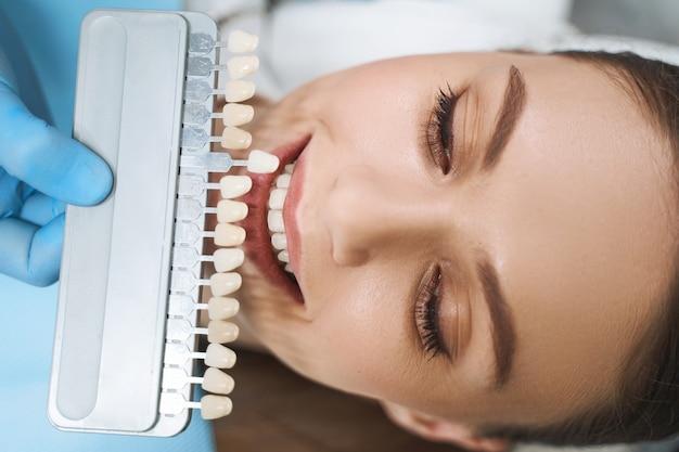Perto de uma garota alegre na cadeira odontológica, escolhendo a cor dos folheados com a ajuda de um médico