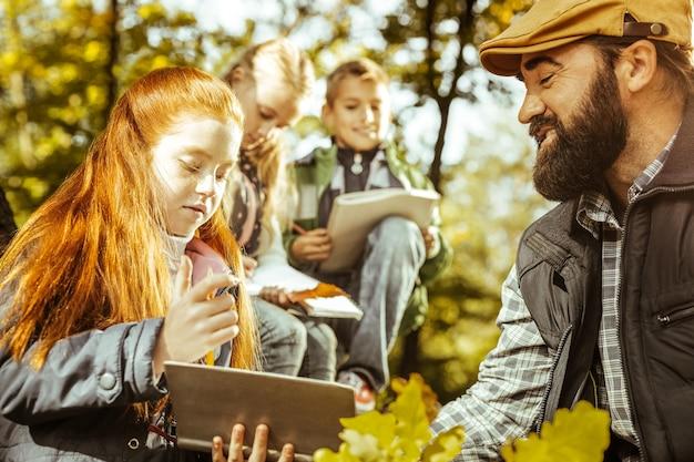Perto de uma garota ruiva e seu professor na floresta em um dia bom