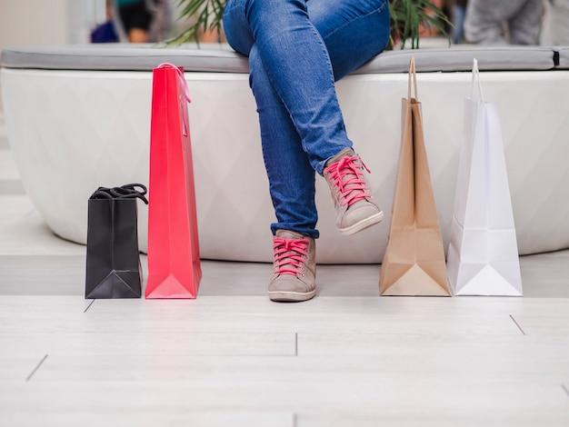 Perto de uma garota sentada com sacos de compras no shopping.