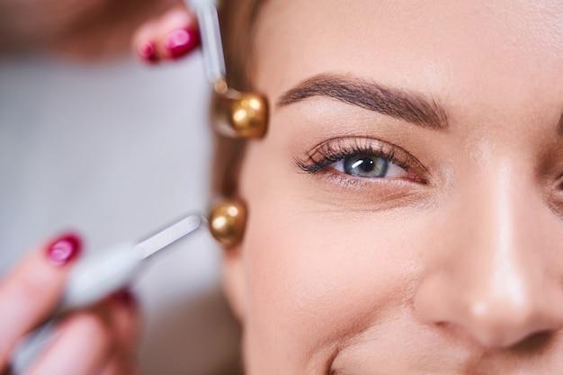 Perto de uma jovem alegre, apreciando o procedimento de microcorrentes para rosto em uma clínica de beleza moderna