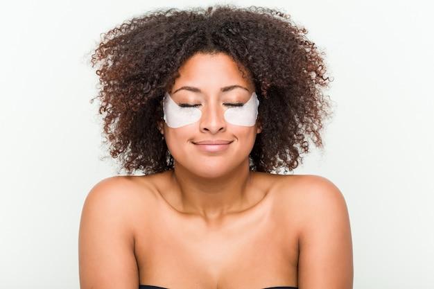 Perto de uma jovem americana africano com um tratamento de pele dos olhos