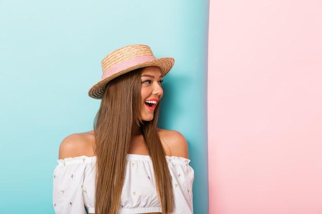 Perto de uma jovem animada com chapéu de verão olhando