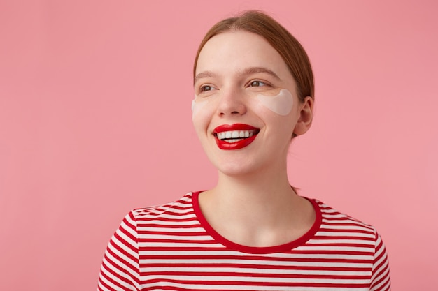 Perto de uma jovem atraente ruiva sorridente com lábios vermelhos e com manchas sob os olhos, usa uma camiseta listrada vermelha, desvia o olhar com uma expressão feliz, fica de pé.