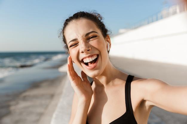 Perto de uma jovem desportista feliz à beira-mar