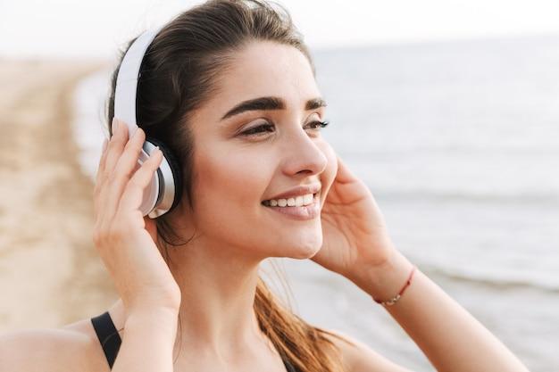Perto de uma jovem desportista feliz em fones de ouvido