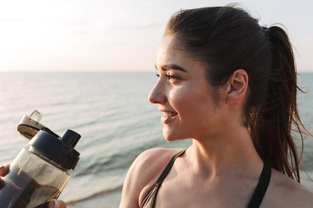 Perto de uma jovem desportista sorridente a beber água