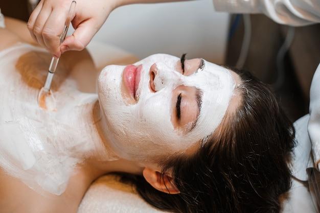 Perto de uma jovem encantadora inclinada com os olhos fechados em uma cama de spa, tendo corpo e máscara facial branca.