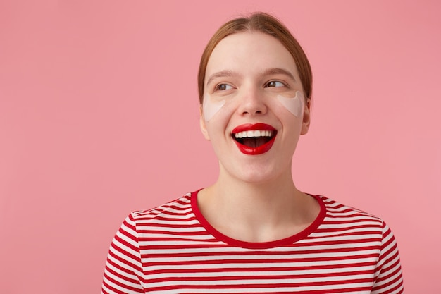 Perto de uma jovem feliz mulher ruiva atraente com lábios vermelhos e com manchas sob os olhos, usa uma camiseta listrada vermelha, desvia o olhar e amplamente sorrindo, fica de pé.