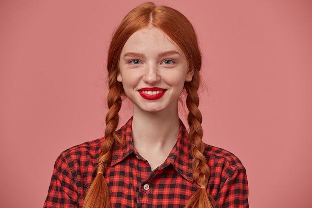 Perto de uma jovem fêmea de gengibre positivo sorri amplamente e mostrando seus dentes brancos para o mundo.