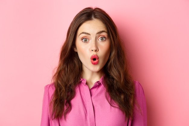 Perto de uma jovem intrigada ofegando, dizendo uau e parecendo impressionado com a câmera, em pé sobre a parede rosa. copie o espaço